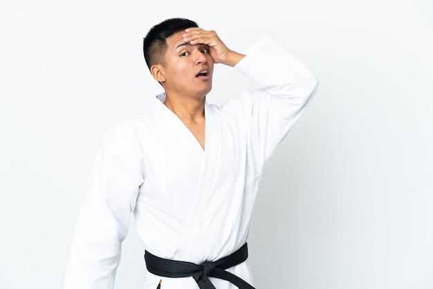 Junger ecuadorianischer mann, der karate lokalisiert auf weißer wand tut, die überraschungsgeste tut, während zur seite schaut