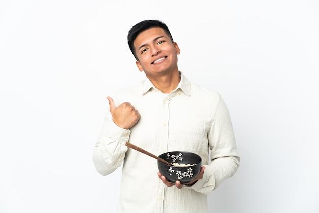 Junger ecuadorianischer mann lokalisiert auf weißem hintergrund, der zur seite zeigt, um ein produkt zu präsentieren, während eine schüssel nudeln mit essstäbchen hält