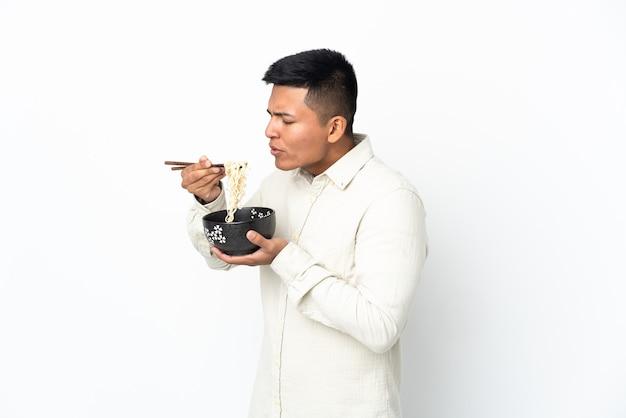 Junger ecuadorianischer mann lokalisiert auf weißer wand, die eine schüssel nudeln mit essstäbchensand hält, der sie bläst, weil sie heiß sind