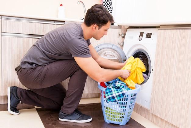 Junger ehemannmann, der zu hause wäscherei tut