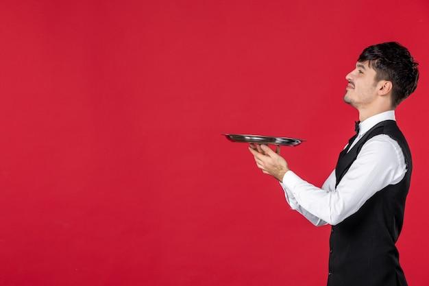 Junger, ehrgeiziger kellner in uniform, der schmetterling am hals hält, der tablett auf isoliertem rotem hintergrund hält
