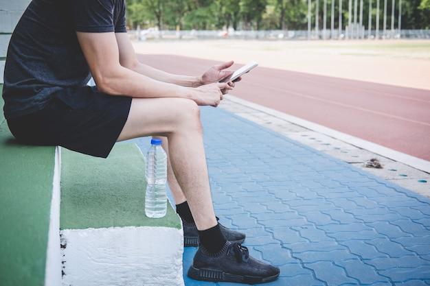 Junger eignungsathletenmann, der auf bank mit der flasche wasser sich vorbereitet, auf straßenbahn zu laufen, übungstrainingswellness stillsteht