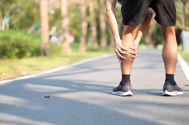 Junger eignungsmann, der seine sportbeinverletzung hält. muskelschmerzen während des trainings