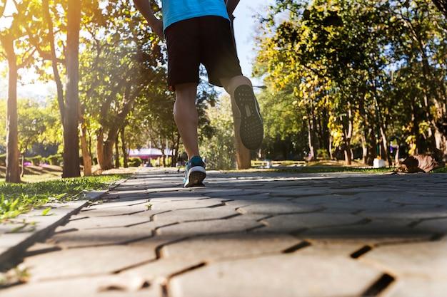 Junger eignungsmannläufer, der auf straße im park läuft