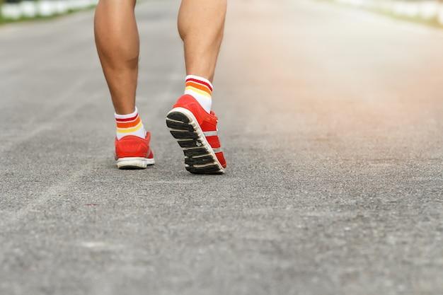 Junger eignungsmannläufer, der auf straße läuft