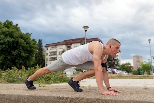 Junger eignungsmannläufer, der beine bevor dem laufen ausdehnt