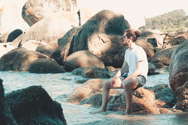 Junger einsamer mann am strand, der in den felsen sitzt und während eines strandtages von der kamera wegschaut, reflexions- und spannungskonzept, kopierraum