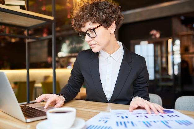 Junger eleganter analyst oder makler, der nach online-daten sucht, während finanzbericht im café erstellt wird
