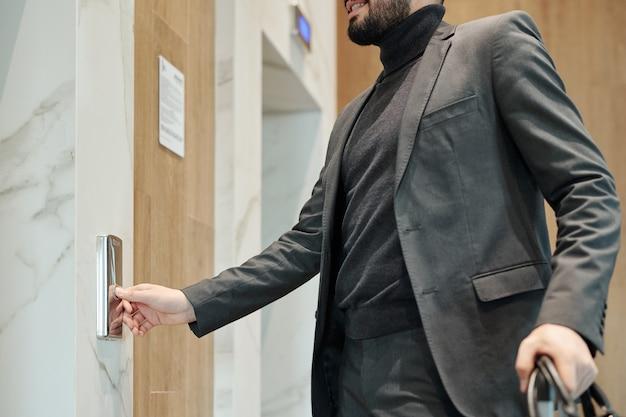 Junger eleganter geschäftsmann, der knopf an der wand drückt, während er durch tür steht und auf aufzug im hotel wartet