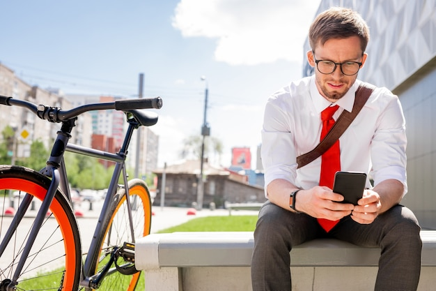 Junger eleganter geschäftsmann, der online-video oder lesende nachricht im smartphone beim sitzen auf bank mit seinem fahrrad in der nähe betrachtet