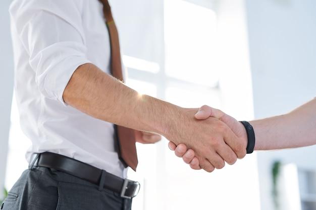 Junger eleganter geschäftsmann, der seinen partner durch handschlag begrüßt, nachdem er vertrag ausgehandelt und unterzeichnet hat