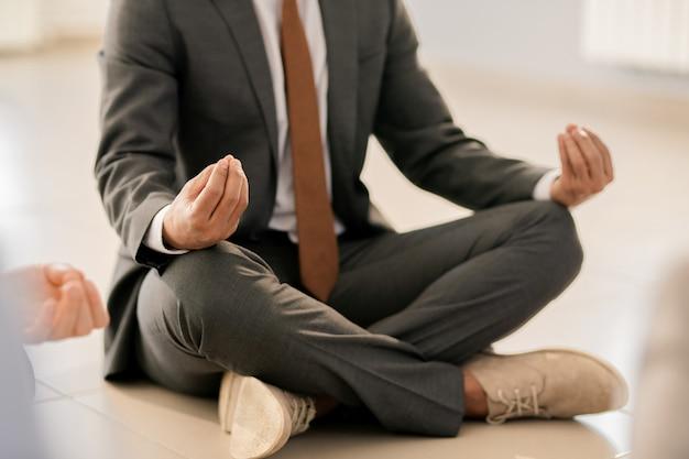 Junger eleganter geschäftsmann in der abendgarderobe, der auf dem boden mit gekreuzten beinen und auf knien zusammengesetzten fingern sitzt