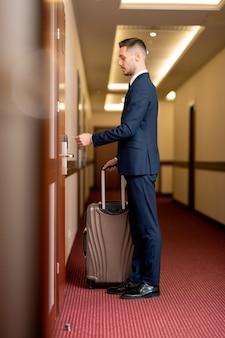 Junger eleganter geschäftsmann in der abendgarderobe mit koffer, der vor geschlossener tür im hotel steht und plastikkarte hält, um den raum zu öffnen