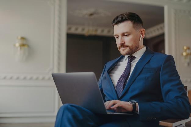 Junger eleganter geschäftsmann in dunkelblauem anzug mit drahtlosen kopfhörern, der zu hause oder im büro mit einem laptop auf einem stuhl sitzt und eine videokonferenz mit dem team oder geschäftspartner hat und auf den bildschirm schaut