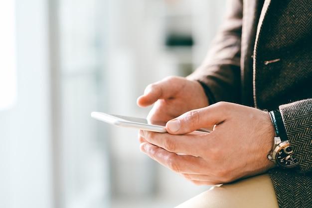 Junger eleganter geschäftsmann mit armbanduhr, die smartphone hält, während durch video-chat oder sms kommuniziert