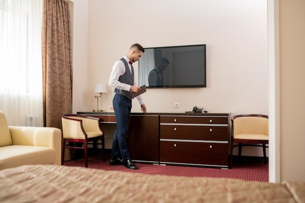 Junger eleganter hotelportier mit digitalem tablett, das stück holzmöbel während der arbeit berührt