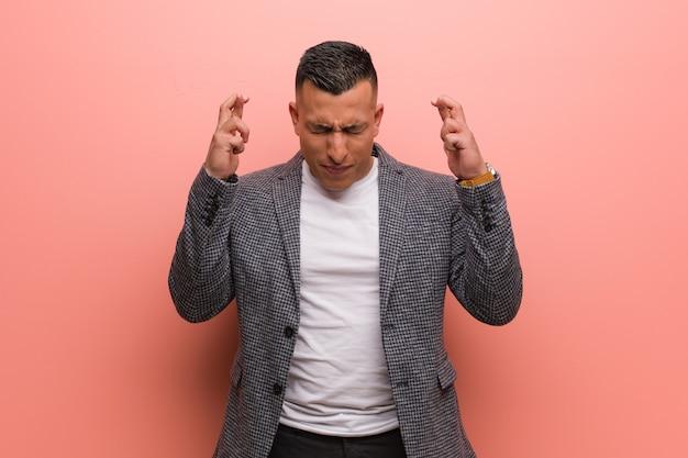 Junger eleganter lateinamerikanischer mann, der finger für glück kreuzt