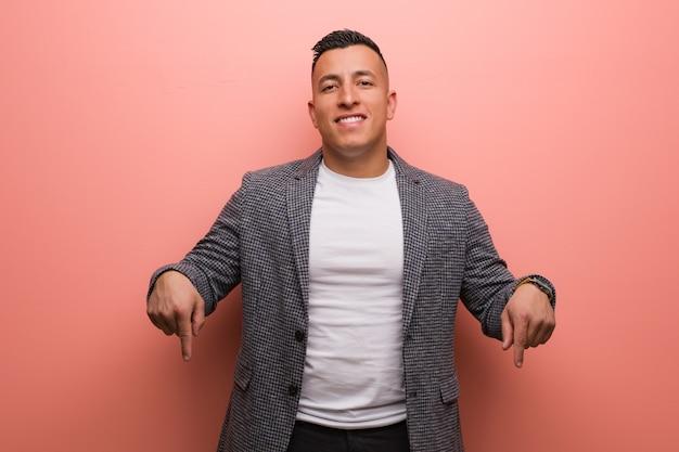Junger eleganter lateinischer mann, der auf die unterseite mit den fingern zeigt