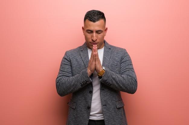 Junger eleganter lateinischer mann, der sehr glücklich und überzeugt betet