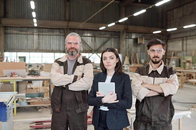 Junger eleganter manager mit touchpad und zwei männlichen arbeitern in der uniform, die arme auf der brust kreuzen, während sie in reihe gegen werkstattinnenraum stehen