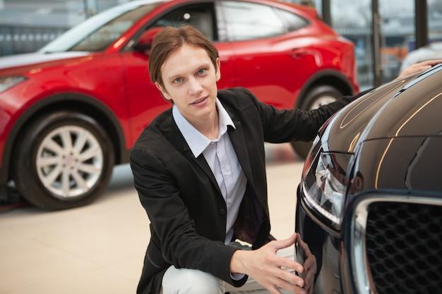 Junger eleganter mann, der zuversichtlich schaut, während er autos im verkauf am händler untersucht