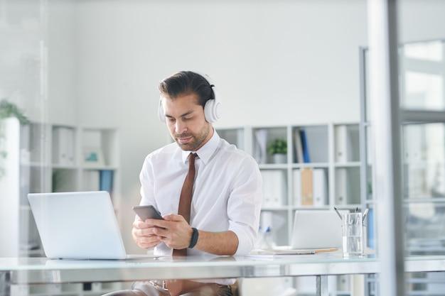 Junger eleganter mann in den kopfhörern, die im smartphone durch arbeitsplatz vor laptop scrollen
