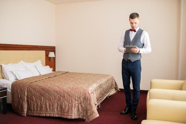 Junger eleganter träger, der digitales tablett verwendet, während er im hotelzimmer neben dem bett steht und durch daten scrollt