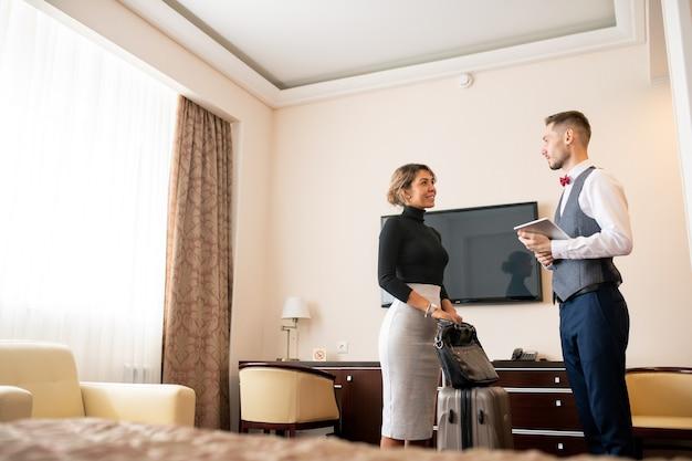 Junger eleganter träger mit touchpad, der mit hübscher geschäftsfrau mit gepäck spricht, während beide im hotelzimmer stehen
