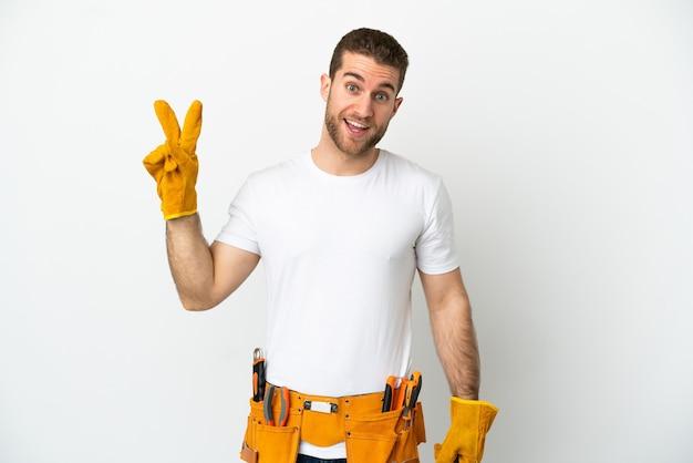 Junger elektrikermann über isolierter weißer wand lächelt und zeigt victory-zeichen