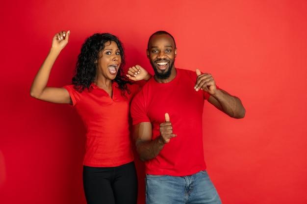 Junger emotionaler afroamerikanischer mann und frau auf rot