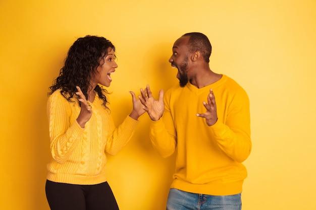 Junger emotionaler afroamerikanischer mann und frau in hellen lässigen kleidern, die auf gelbem raum aufwerfen