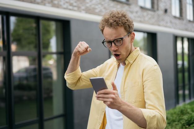 Junger emotionaler mann, der online-tv mit einer mobilen app für sportwetten sieht