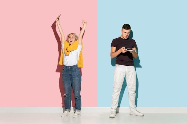 Junger emotionaler mann und frau auf rosa und blau