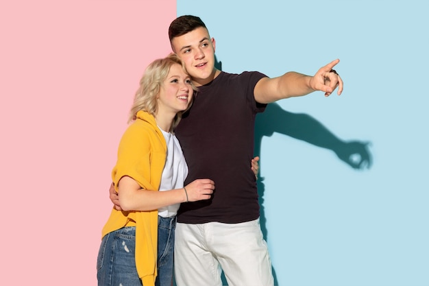 Junger emotionaler mann und frau auf rosa und blauem hintergrund