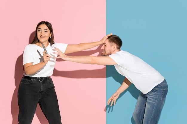 Junger emotionaler mann und frau auf rosa und blauer wand
