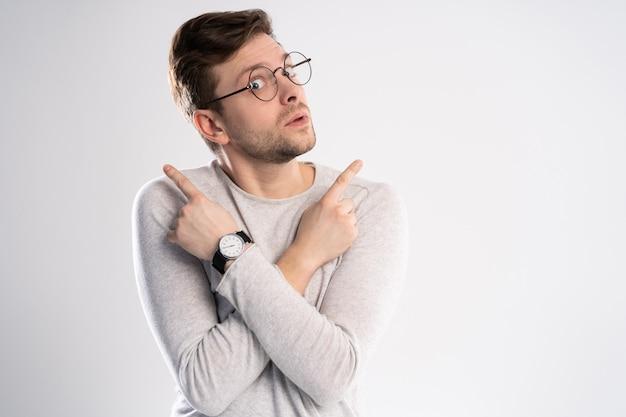Junger emotionaler sorgloser mann lokalisiert auf weißem hintergrund