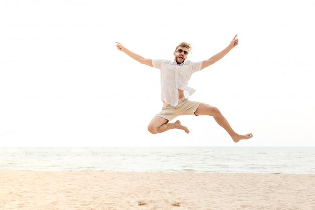 Junger energischer glücklicher mann, der am strand springt