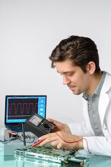 Junger energischer männlicher techniker oder ingenieur repariert elektronische geräte