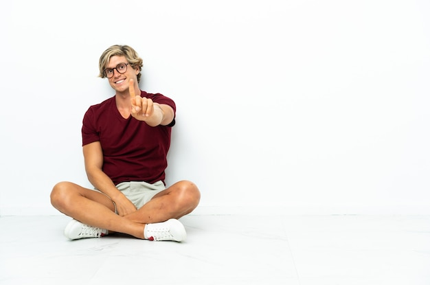 Junger englischer mann, der auf dem boden sitzt und einen finger hebt