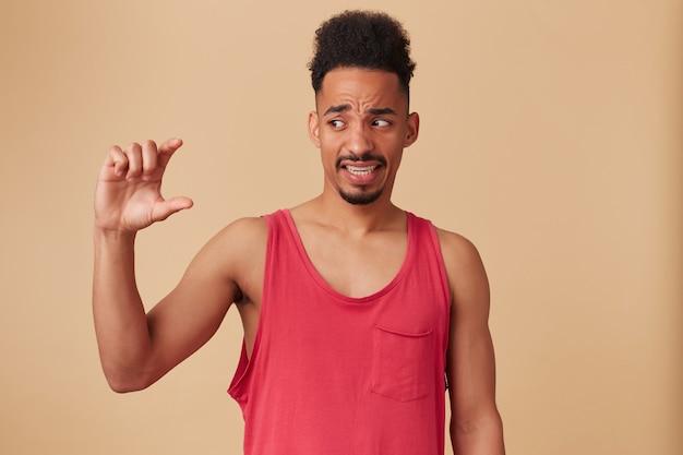 Junger enttäuschter afroamerikaner, bärtiger kerl mit afro-frisur. trage ein rotes trägershirt. zeigt ein wenig größe und schaut es mit ekel über pastellbeige wand an