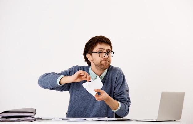 Junger enttäuschter, verzweifelter gutaussehender kerl, unternehmer zerreißt dokumente, enttäuscht von schlechtem bericht