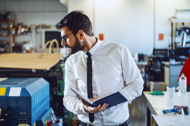Junger erfahrener kaukasischer bärtiger grafikingenieur mit brillen, die notizbuch halten und auf druckmaschine überprüfen, während in druckerei stehen.