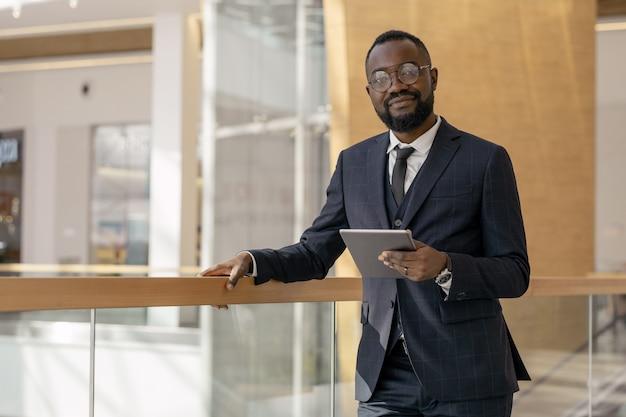 Junger erfolgreicher afrikanischer angestellter mit tablet, der dich anschaut