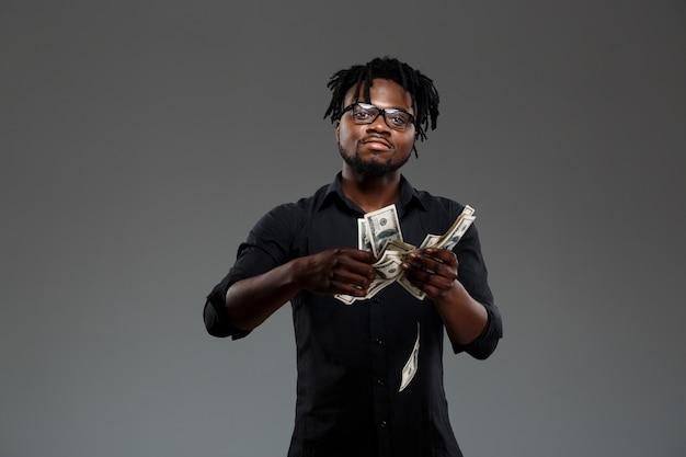 Junger erfolgreicher afrikanischer geschäftsmann, der geld auf dunkelheit wirft