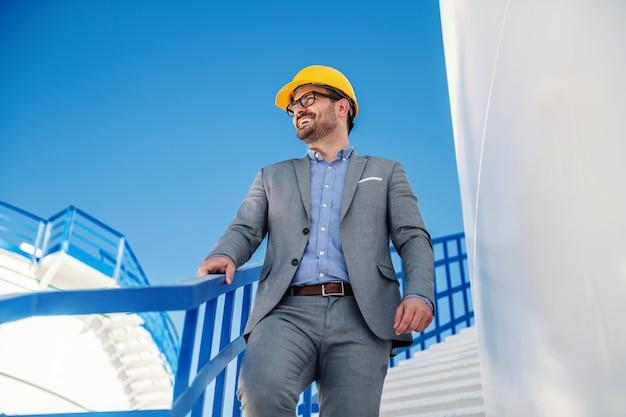Junger erfolgreicher attraktiver lächelnder positiver kaukasischer geschäftsmann im anzug mit helm auf kopf, der die treppe hinuntergeht und sich umschaut.