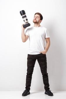 Junger erfolgreicher berufsfotograf im weißen t-shirt verwendet eine digitalkamera mit einem langen objektiv