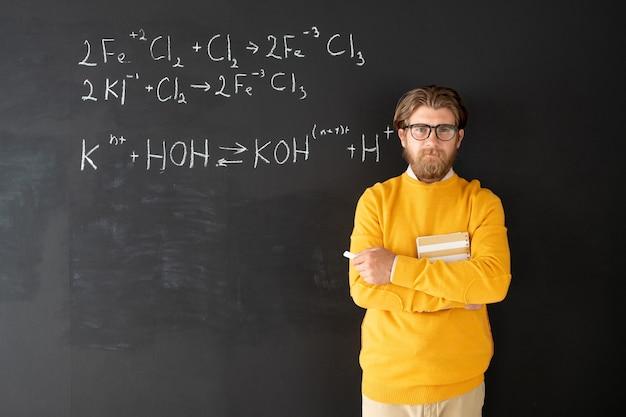 Junger erfolgreicher chemielehrer in freizeitkleidung, der gegen tafel mit chemischen formeln vor online-publikum steht