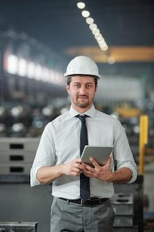 Junger erfolgreicher eleganter vorarbeiter im schutzhelm unter verwendung des digitalen tabletts am arbeitsplatz in der zeitgenössischen industrieanlage