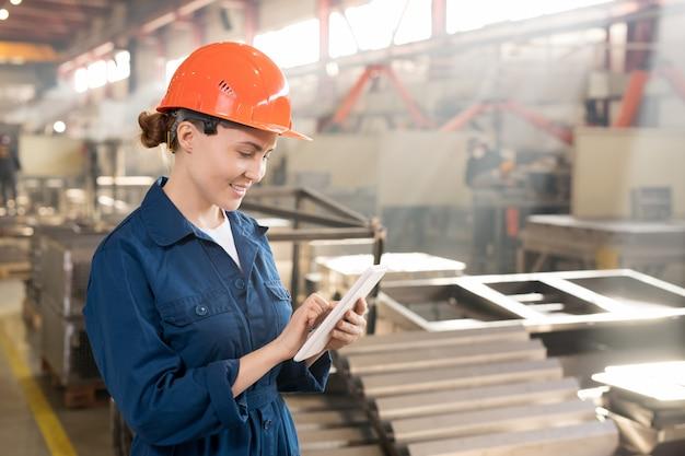 Junger erfolgreicher fabrikarbeiter in arbeitskleidung und helm, die im touchpad beim suchen nach technischen daten scrollen
