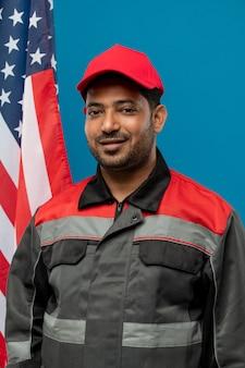Junger erfolgreicher fabrikarbeiter oder handwerker der gemischten rasse in der arbeitskleidung, die vor der kamera mit sternenbanner auf blau steht